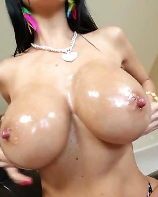 busty brunette oils up her fat boobs